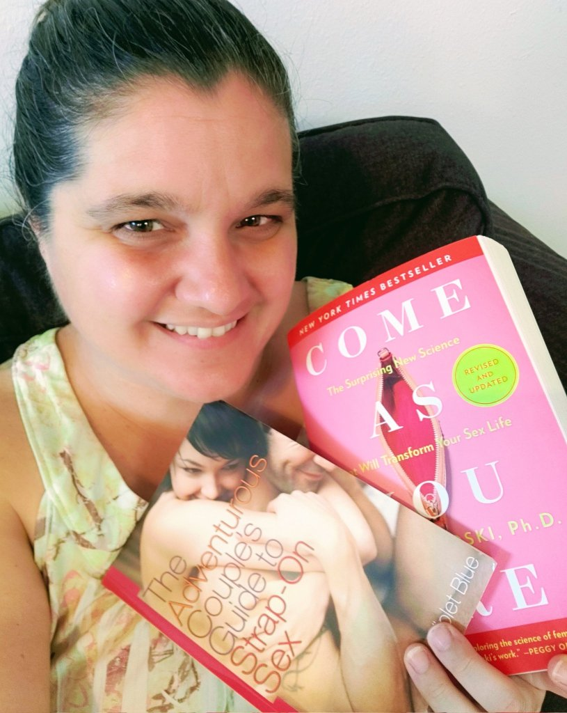 image of me holding two books: the adventurous couple's guide to strap-on sex by violet blue, and come as you are by emily nagoski, ph. d.
