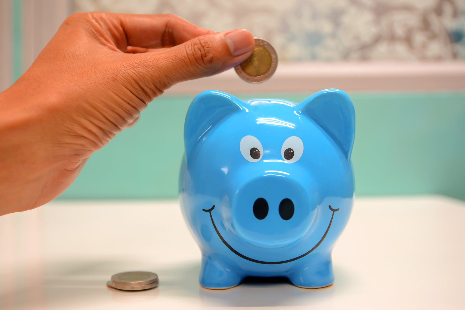 photo of a hand placing a coin in a smiling blue piggy bank